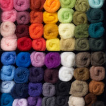 box containing 56 different different coloured carded New Zealand Maori felting wool batts